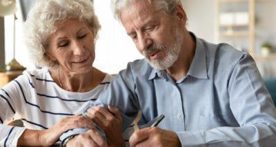 Älteres Ehepaar unterschreibt einen Bestattungsvorsorgevertrag