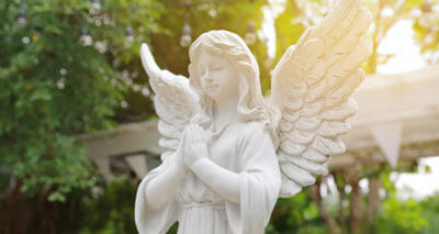 Keramik-Engel vor grünen Blättern
